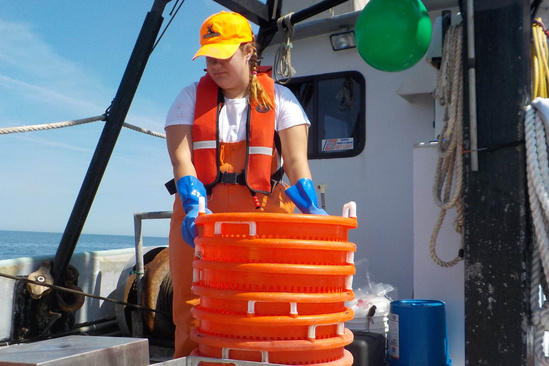 A woman in an orange life vest and yellow hat with blue gloves holds a stack of orange plastic bins
