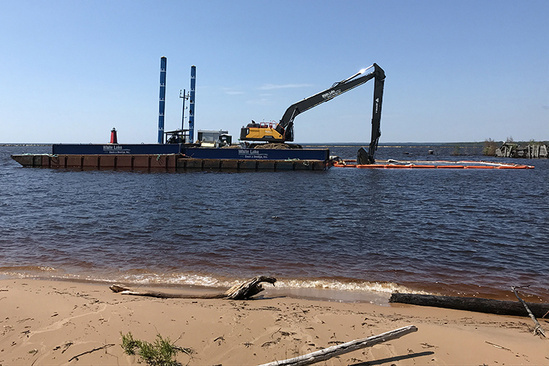 A backhoe floats on a barge, floating on water and pulling sediment out of the water