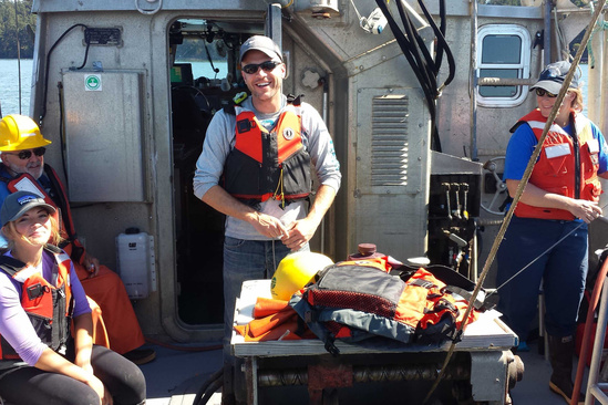 A veteran intern and NOAA staff smile for a picture as they're on a boat conducting field research.