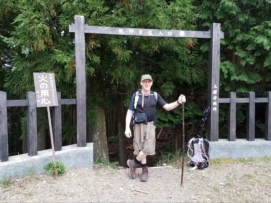 Hiker posing with Japanese hiking path signage.