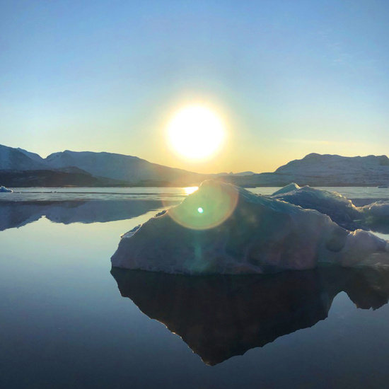 Water smooth as glass as the sun rises over mountains lining the Qaqortoq fjord in southwest Greenland.