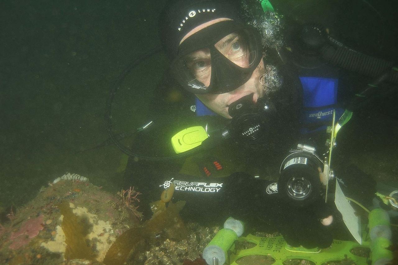 Bill Hagey holding time-lapse image camera used to study abalone movements.