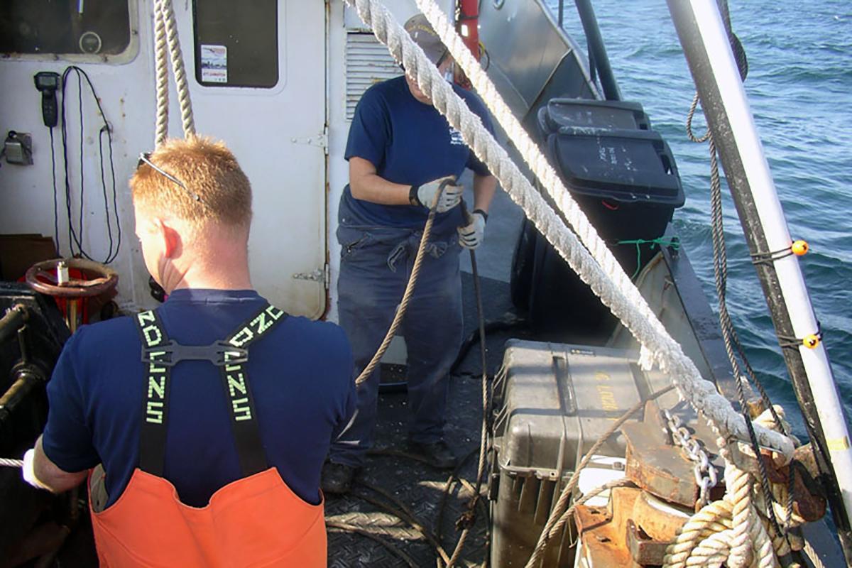 Two crew members aboard vessel working.