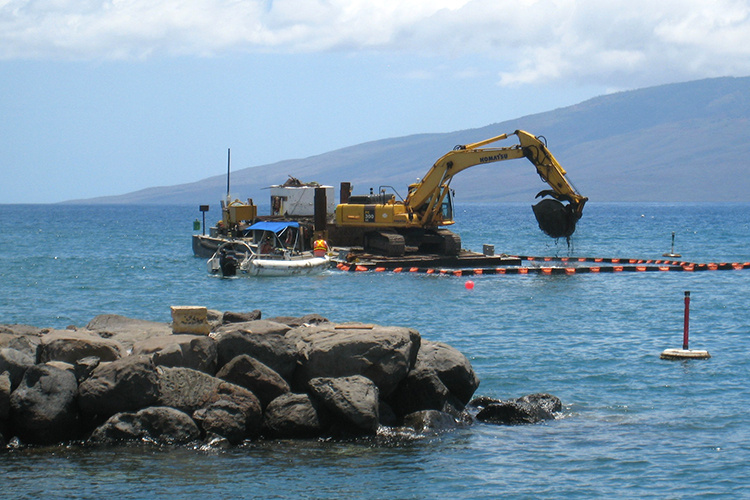 A excavator on a barge digging mud/sand from a harbor.
