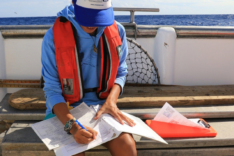 Fisheries observer on a vessel recording data on paper.