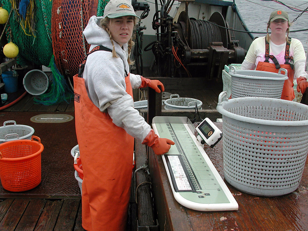 female scientists measuring samples on back deck with buckets of fish.jpg