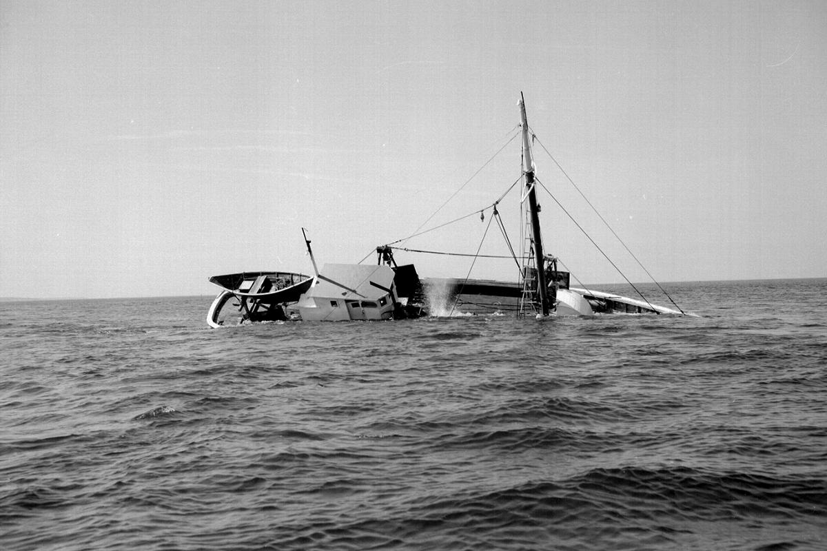 A fishing vessel tipped on its side in ocean
