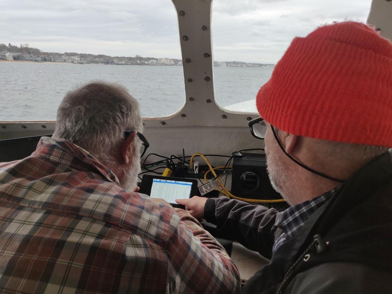 fishermen in wheelhouse reading data on a small display