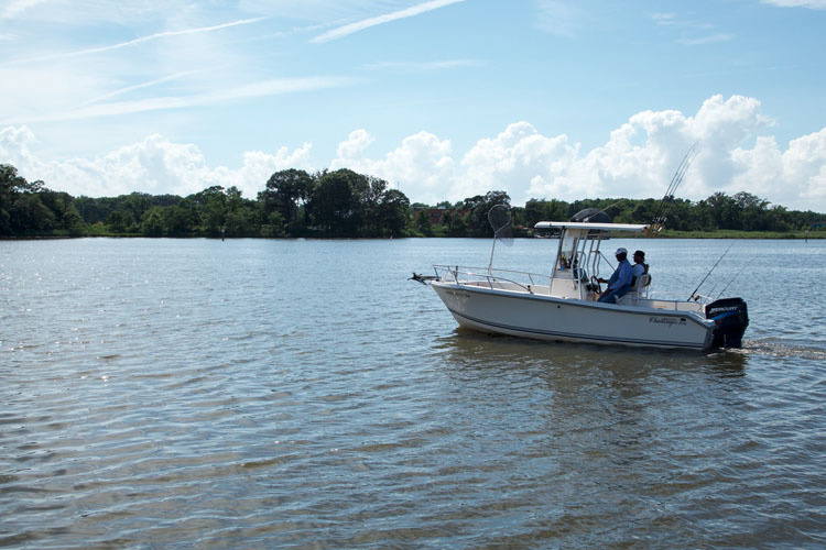 Two anglers sit at the wheel of a private boat on the Chesapeake Bay.