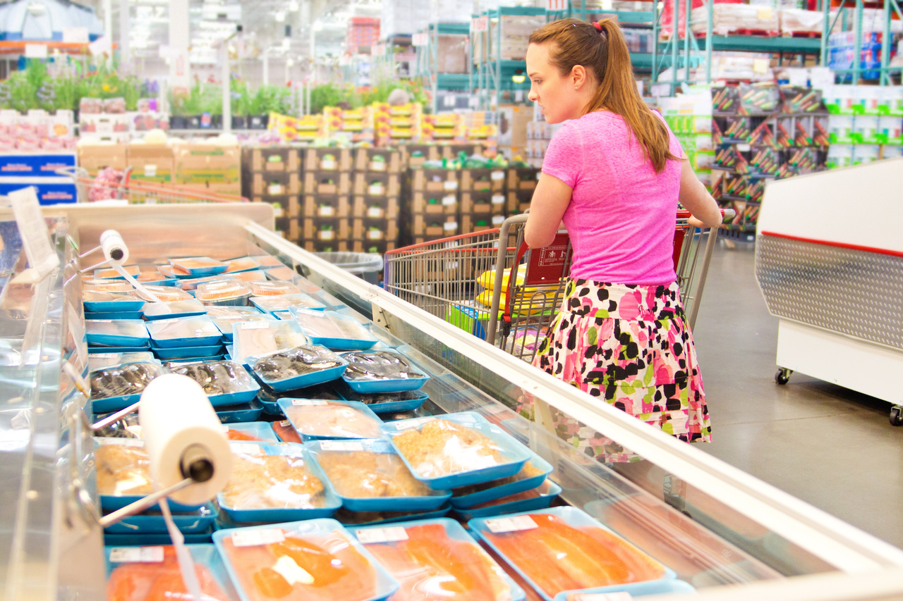 Grocery shopper considering healthy seafood choices.