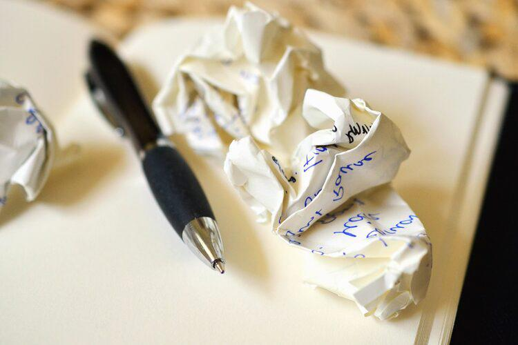Ballpoint pen and crumpled paper with writing on it atop an open blank journal