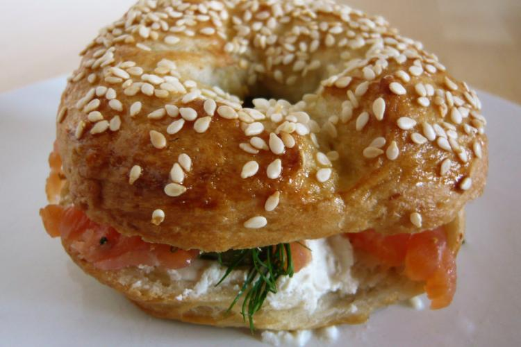 Photo of a sesame bagel sandwich with lox and schmear.