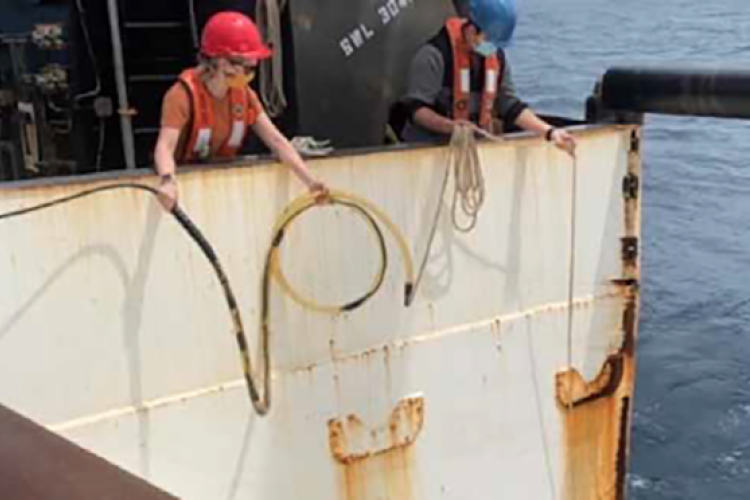 Two researchers on the deck of a research ship at sea wearing summer clothing, hard hats, and cloth masks to protect against COVID-19 transmission. They are easing an underwater sound recorder attached to a cable over the side and into the water. It is daylight and the weather is calm.