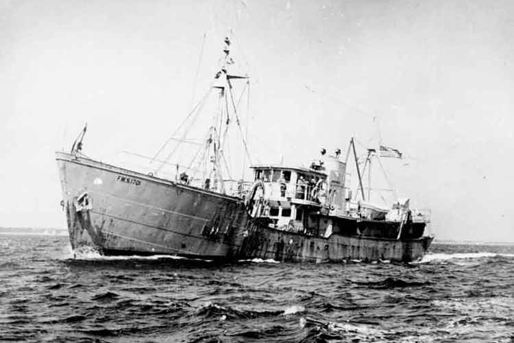 The Albatross III at sea, crew members visible near wheel house.