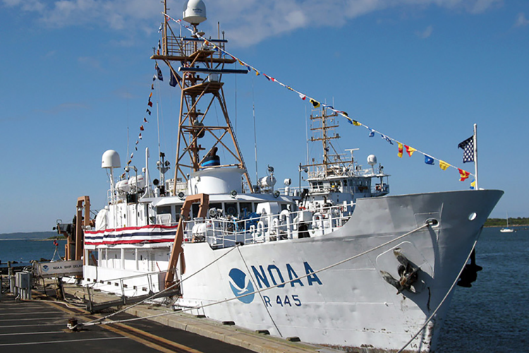 NOAA white boat, the Delaware II with celebration banners and flags tied to the dock.