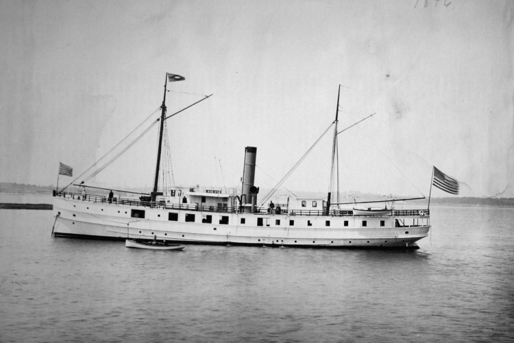 Steamer sailor anchored, American flag flying from stern.
