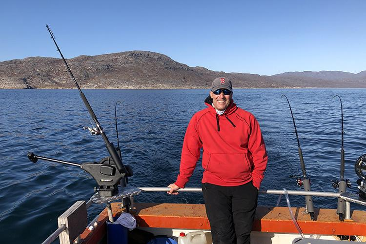 Tim Sheehan at stern of boat, fishing gear set up for trawling in the waters off Greenland.