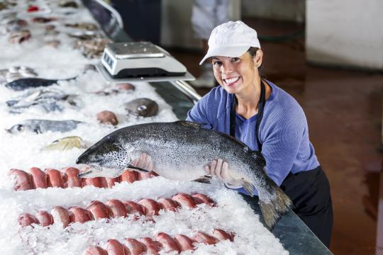Woman holding fish at seafood counter.