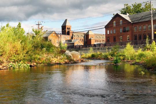 A river flows past several historic brick buildings