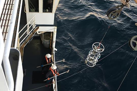 Aerial view of two crew members wearing hard hats at the rail on the main desk of the research vessel. They stand ready to snag a piece of water sampling equipment as it is raised from the water by a winch, using gaffs designed for this purpose.