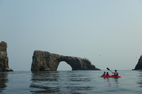 Three people in a red kayak paddle near a large stone arch.