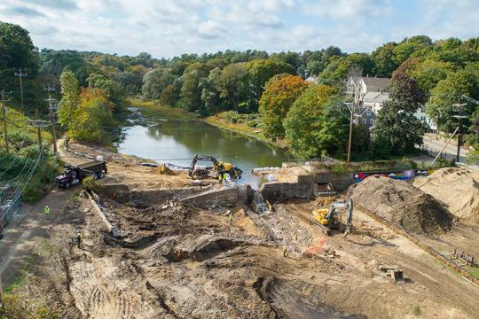 Aerial view of construction equipment removing a dam from a stream