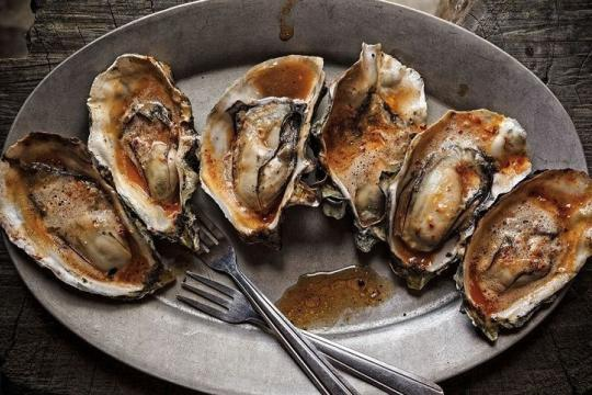 Six grilled Hog Island oysters drizzled in barbecue chipotle butter, on a serving dish with two small forks.