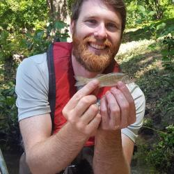 Picture of Jonathan Watson holding a small fish.