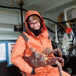 Photo of Allie Conrad holding a large crab.
