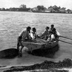 4 men in a dory being pushed to sea by Baird.