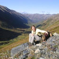 Diane Borggaard on a hill in Alaska with her dog.