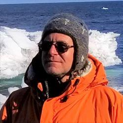 Chris is wearing a grey colored cap standing in front of icechunks in blue ocean