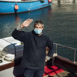 Man in mask waving from boat.