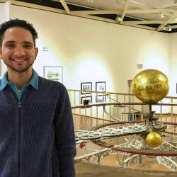 Science writer standing in front of a solar system installation in a musuem.