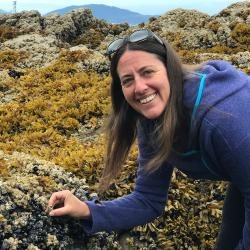 Photo of Stori Oates inspecting barnacles in a rocky tidal shore zone.
