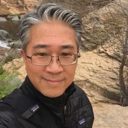 Selfie photo of Jim Lee with high desert rocks and mountain stream in the background.