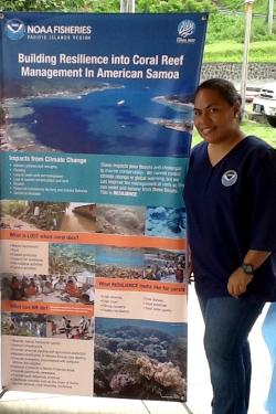 Fatima Sauafea-Le'au, Fisheries Biologist, standing next to vertical banner at an outreach event
