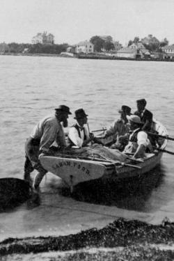 five men seated in a small boat named Sarah Ford in sallow water by the shore, another man with beard (Spencer Baird) ready to push it off. Buildings are visible in the background along the far shore