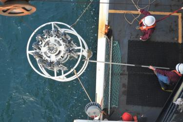 White circular object above the water with lines and a hook attached.