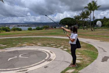 NOAA student intern taking pictures of NOAA IRC Hawaiian compass art.