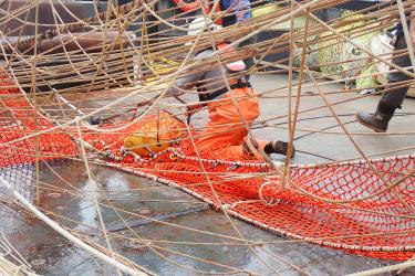 Figure kneeling on deck with a piece of equipment through the net mesh