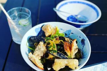 Beer steamed mussels in a bowl with crusty bread.
