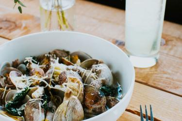 A bowl of cooked clams in sauce, sprinkled with cheese.