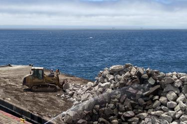 A bulldozer pushes large rocks off a barge into the water.