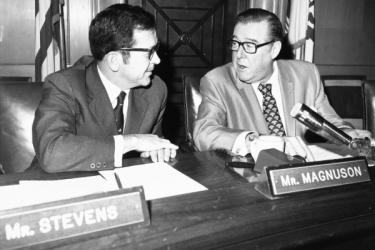 U.S. Senators Ted Stevens (R-AK) and Warren Magnuson (D-WA) having a conversation in their neighboring senate seats, with state flags in the background.