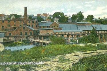 Red paper mills with black roofs along the river in Gardiner, Maine