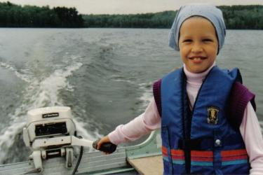 smiling little girl steering a boat on a lake