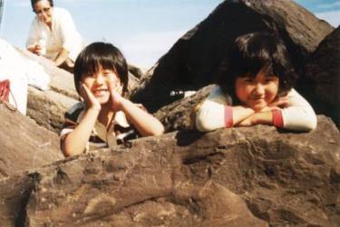 two smiling kids on rocky shore
