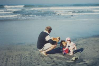 young girl on the oregon shore with her father, holding a red bucket.