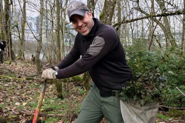 A man in the woods digging a hole with a shovel.